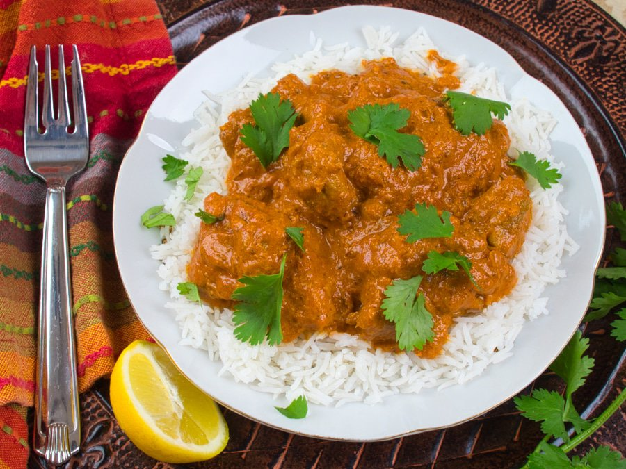 Easy Butter Chicken (Murgh Makhani)Served on a bed of rice and garnished with cilantro.