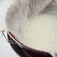 How to Make Paneer - Cheesecloth in a strainer with the cheese curds beginning to drain off the whey.