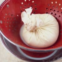How to Make Paneer - The cheesecloth twisted around the cheese waiting for a weight to continue pressing out the whey.