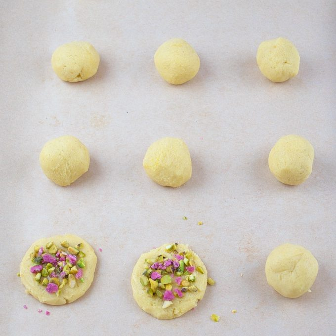 Cardamom Cookies with Rose Water shaped into balls and garnished with candied rose petals and chopped pistachios.