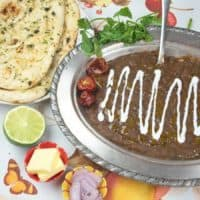 Black Lentil Dal (Dal Makhani) Served in a silver bowl with naan, limes and ghee.
