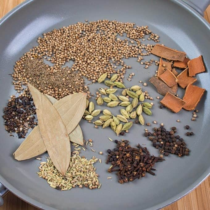 Garam Masala Powder Whole spices in a large pan ready to be toasted.