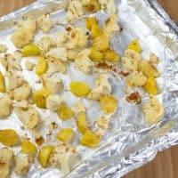 Cauliflower Potato Curry (Aloo Gobi) Potatoes and bite-sized cauliflower roasting on a baking sheet.