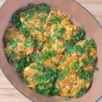 Easy, Enticing Chicken Biryani - The chicken layer garnished with green herbs.