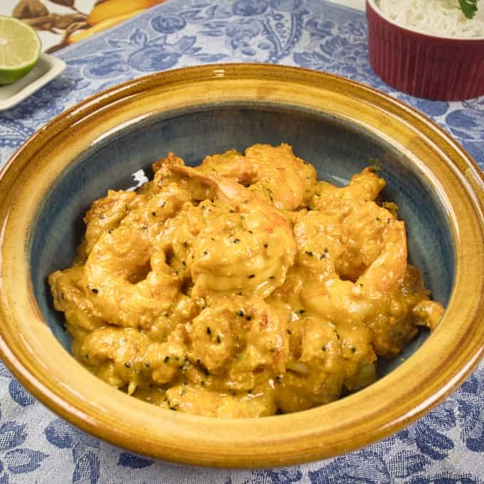 Bengali Prawn Curry (Chingri Posto) Served in a beautiful gold and blue dish with rice and lime on the side.