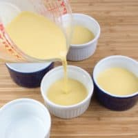Sweet & Creamy Chai Pudding - Pouring the steeped cream into four ramekins in a baking dish.