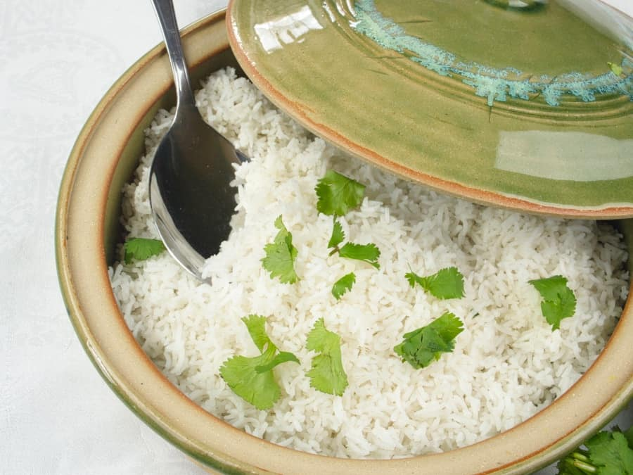 Stovetop Basmati Rice served with a green flutter of cilantro in a lidded ceramic pot.