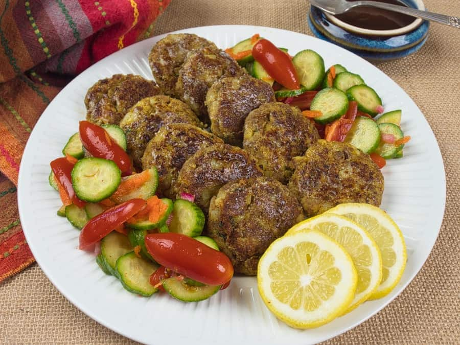 Indian Spiced Kebabs (Kavab) served with cucumber and tomato salad.