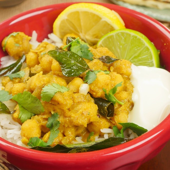 Comforting Coconut Chickpea Curry (Kerala Kadala) Served over rice with a dollop of raita and wedges of lime.