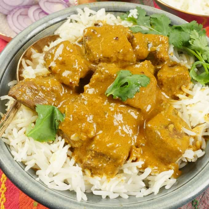 Coconut Lamb Curry (Madras Curry) Served on a bed of fluffy basmati rice, garnished with fresh cilantro leaves.
