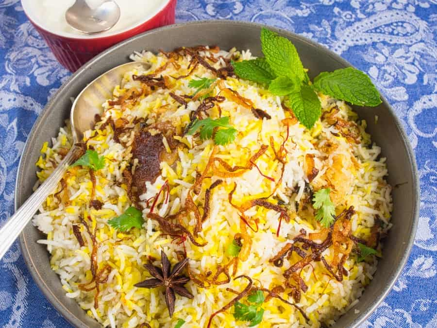 Easy, Enticing Chicken Biryani served up in a large grey ceramic serving dish graced with crispy brown onions, star anise and red saffron.