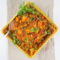 Roasted Eggplant Curry (Baingan Bharta) Beautiful redish orange eggplant curry in a square gold serving bowl garnished with a dusting fresh green cilantro