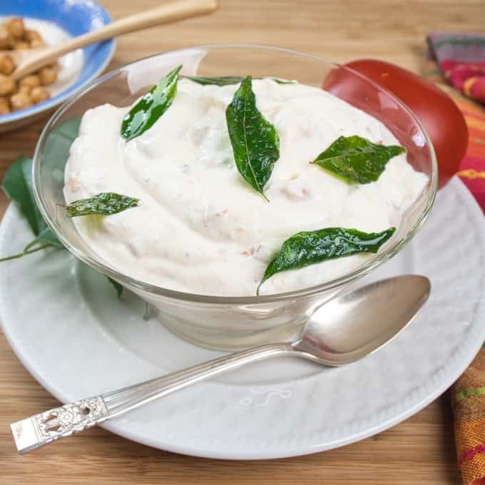 Cooling Tomato Raita - An Indian yogurt salad flavored with tomato and spices and garnished with fried curry leavesA perfect side for anything you are eating.
