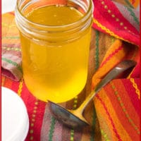 Easy Homemade Ghee Clarified butter all golden and ready to stand by the stove.