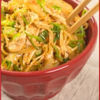 20-Minute Sichuan Noodles served up in a red bowl with chopsticks.