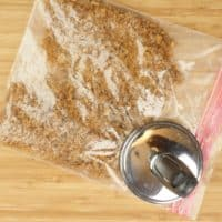 Cardamom Pumpkin Cheesecake (No-Bake) crushing cookie crumbs in a resealable bag