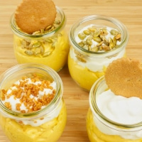 Cardamom Pumpkin Cheesecake (No-Bake) four small jars of cheesecake all garnished differently: with candied pumpkin seeds, whipped cream and whole ginger cookies