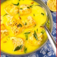 Coconut Fish Curry (Kerala Molee) Served in a pottery bowl garnished with fried curry leaves and a wedge of lemon.