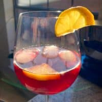 Pomegranate Cocktail or Mocktail - Served with a slice of lemon in a red wine glass.