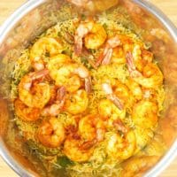Instant Pot Shrimp Birayani (Kerala-Style) shrimp topping a bed of spiced rice ready for cooking in an Instant Pot.