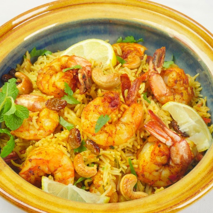 Instant Pot Shrimp Biryani (Kerala-StyInstant Pot Shrimp Biryani (Kerala-Style) Shrimp biryani ready to be served in a pretty pot dressed with slices of lemon, topped with toasted cashews and raisins, and a dusting of fresh herbs.