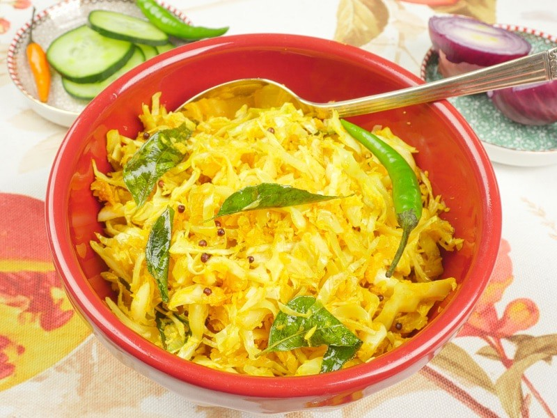 Cabbage Stir-Fry (Kerala Thoran) Served in a pretty red bowl garnished with fried curry leaves.