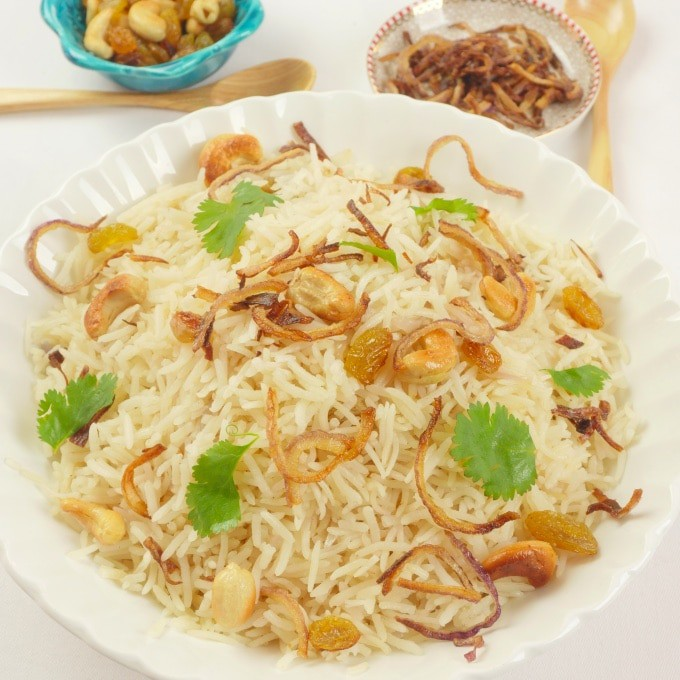 Simple Ghee Rice (Nei Choru) - Ghee rice beautifully garnished with cashews, raisins, birista (browned onions) and a flutter of cilantro.
