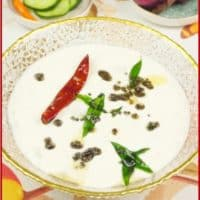 Cucumber Raita (Kerala Pachadi) Presented for serving in a gold-rimmed bowl and showered with a tadka of curry leaves, a dry red chili and mustard seeds.