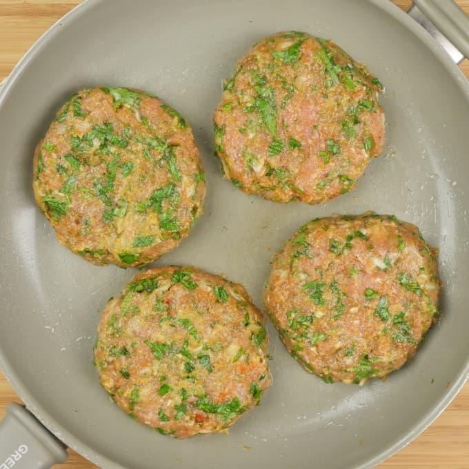 Indian-ish Turkey Burger raw patties beginning their cooking in a large frying pan.