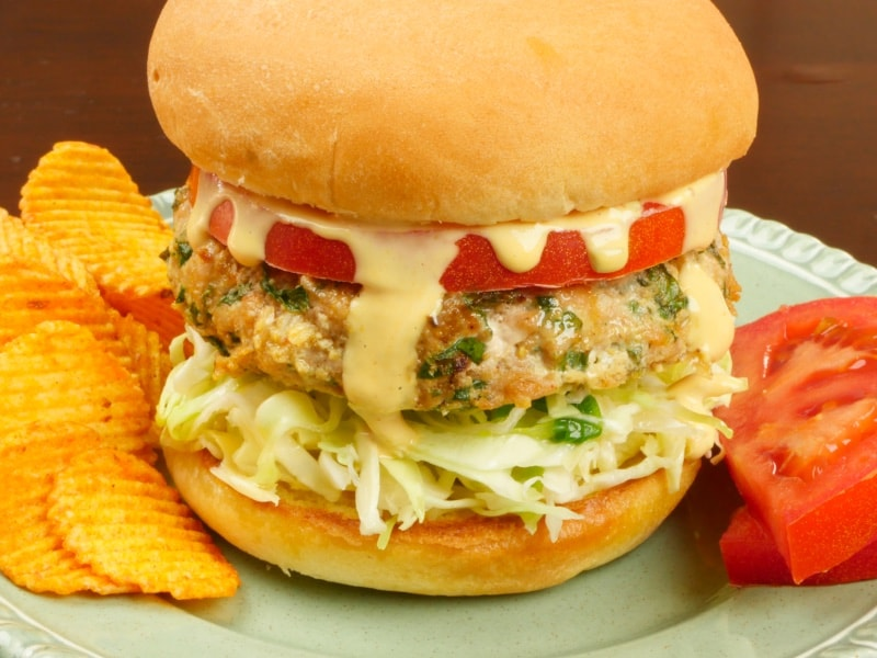 Indian-ish Turkey Burger serve with masala chips and sandwiched with a big slice of tomato, a simple slaw, and a generous drizzle of Sam's burger sauce between toasted buns.