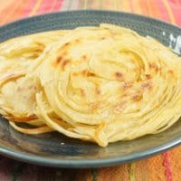 Layered Indian Flatbread (Kerala Parotta) Stacked on a pretty plate ready to be devoured.