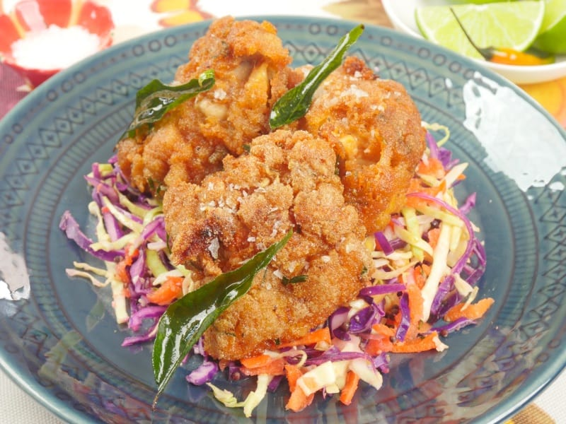 Kerala Fried Chicken All beautifully fried and golden brown, resting on a bed of a multi-colored cabbage and carrot salad.