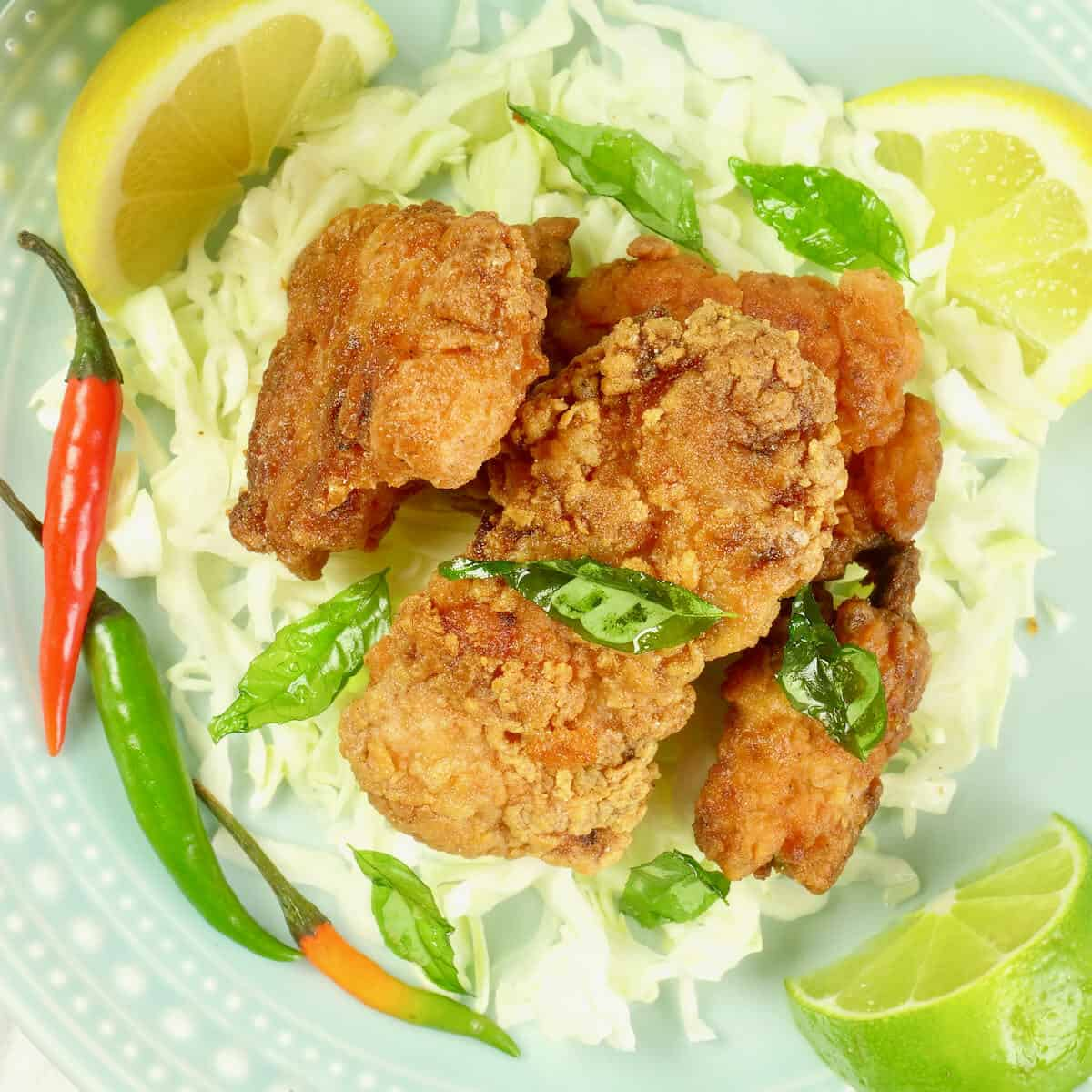 Kerala Fried Chicken Served with lemon wedges, and spray of fried curry leaves, a beer, on a bed of sliced green cabbage.