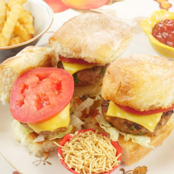 Chicken Burger Kerala-Style Mini burgers all dressed up with tomatoes, cheese, sev and masala chips.