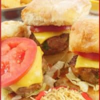 Mini burgers all dressed up with tomatoes, cheese, sev and masala chips.
