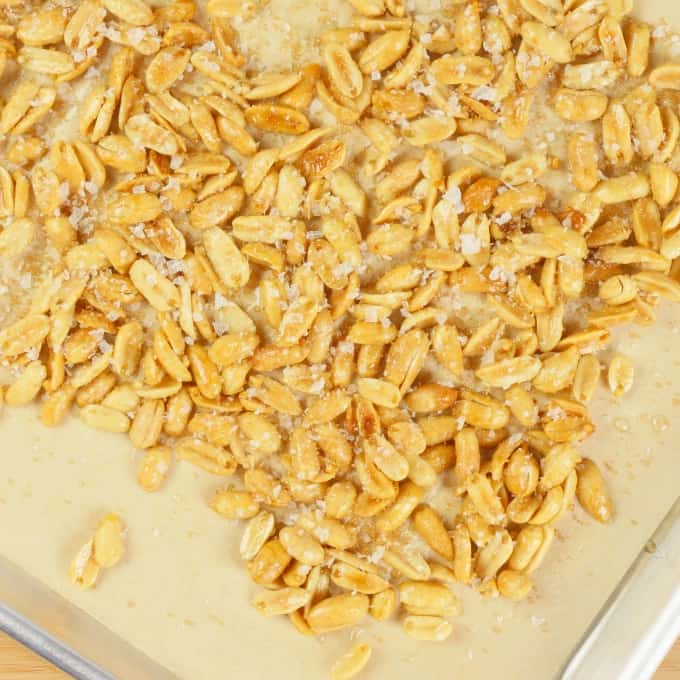 The nuts oasting on a sheet pan in the oven.