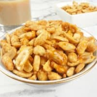 Easy Sweet and Salty Nuts Roasty, salty an sweet nuts all served up in a gold rimmed bowl.