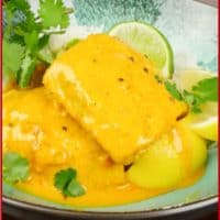 Kerala Fish Curry Slow Baked Served atop a bowl of rice, garnished with lemon wedges and a sprinkling of fresh cilantro.