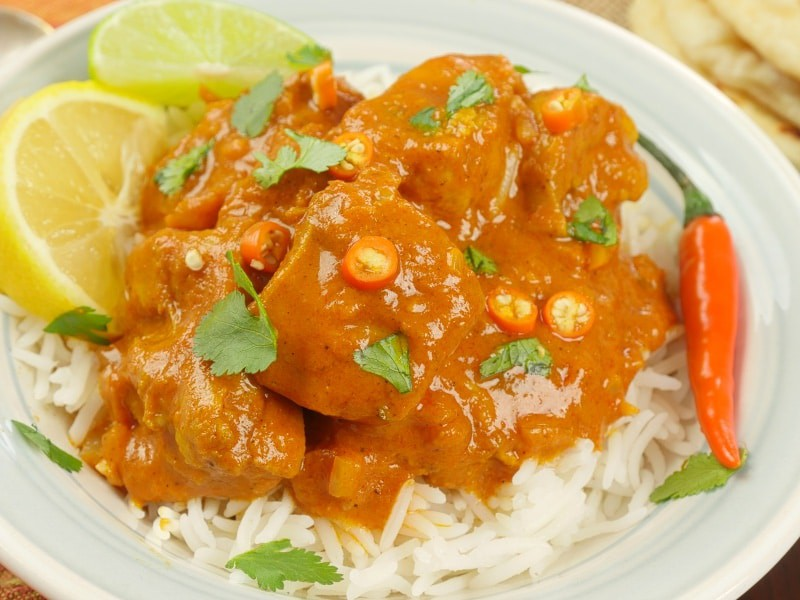 Kerala Chicken Curry Served with a dusting of cilantro and small slices of fresh orange chilies on a bed of rice.