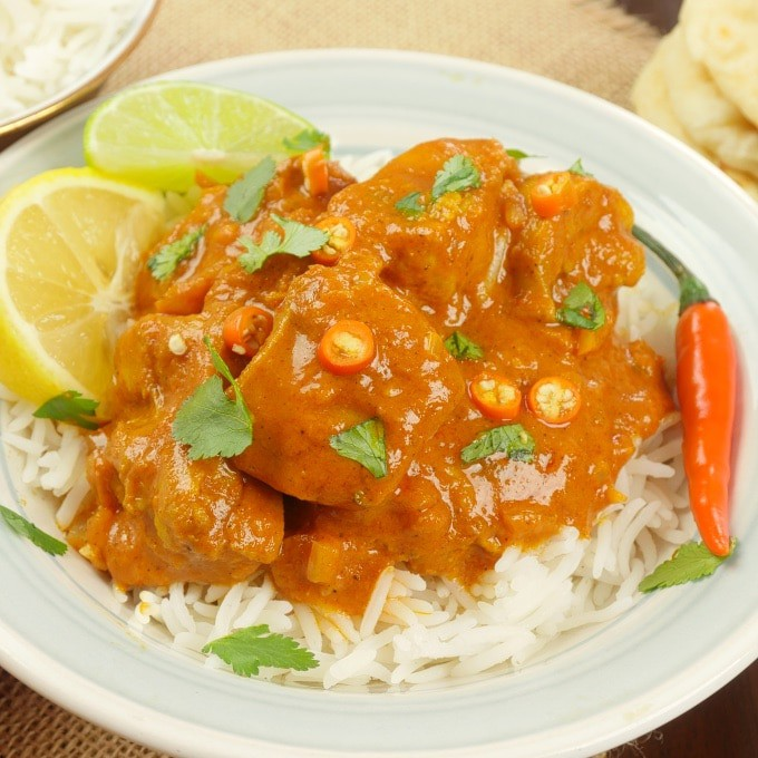 Served with a dusting of cilantro and small slices of fresh orange chilies on a bed of rice.