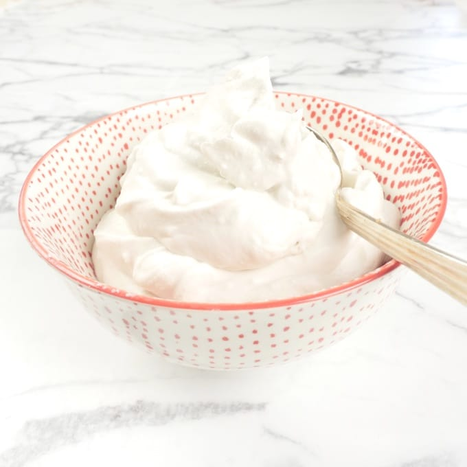 Easy Coconut Whipped Cream In a pretty red bowl and ready to do it's duty and top indiscriminately.