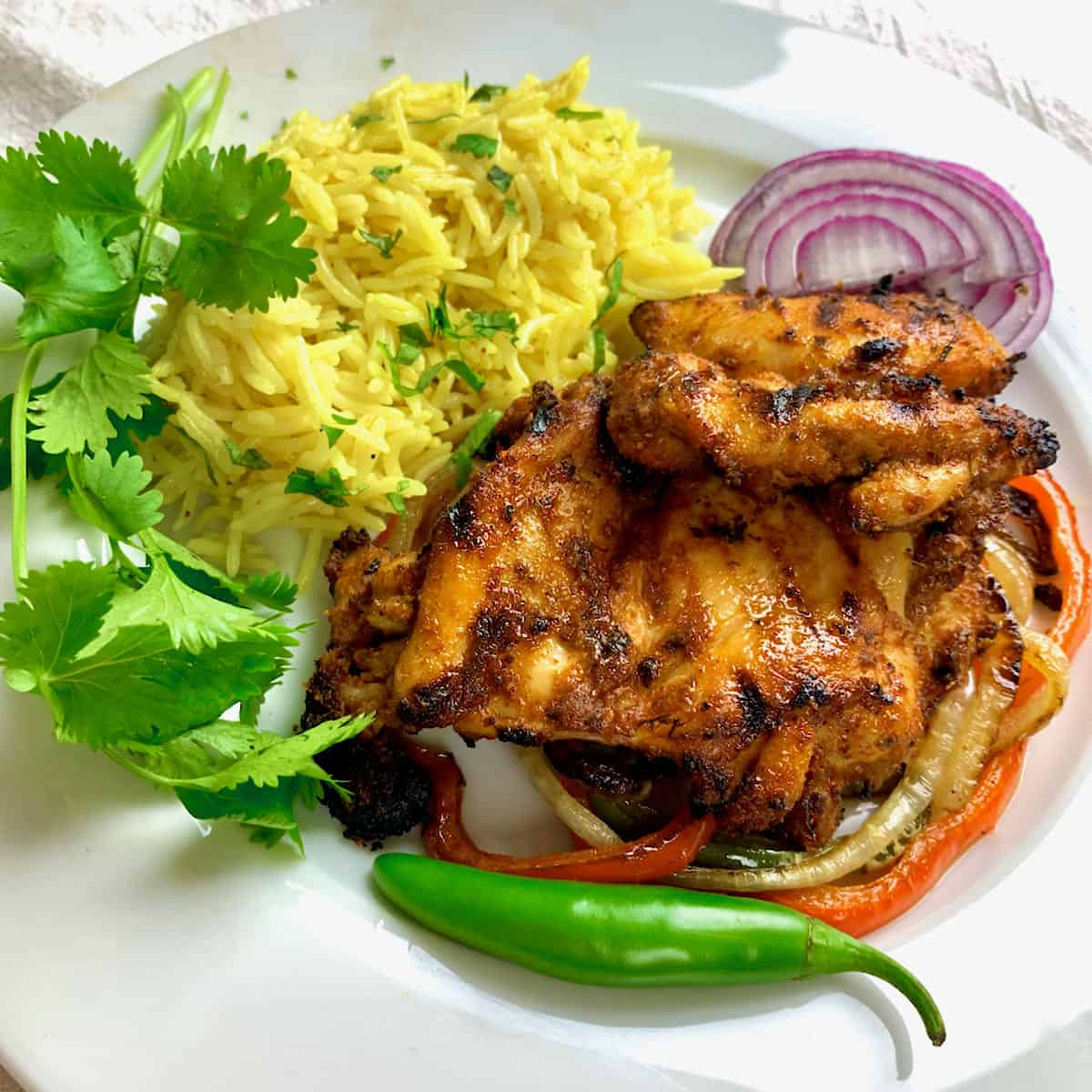 Skinless, boneless tandoori chicken thighs on a bed of bell peppers with a side of turmeric yellow rice.