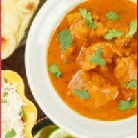 Instant Pot Chicken Tikka Masala Served with a side of paratha, a flutter of cilantro leaves, and wedges of lime.