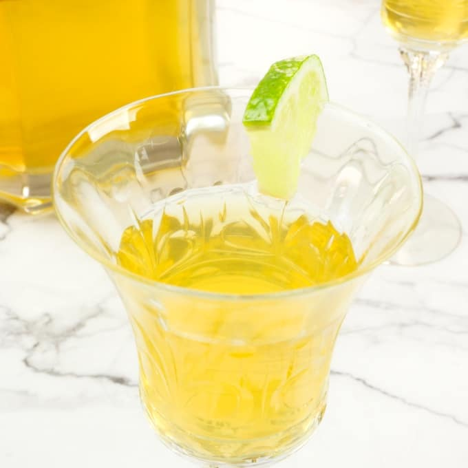 Easy Homemade Mango Liqueur Served up in a sweet little liqueur glass and slice of lime.
