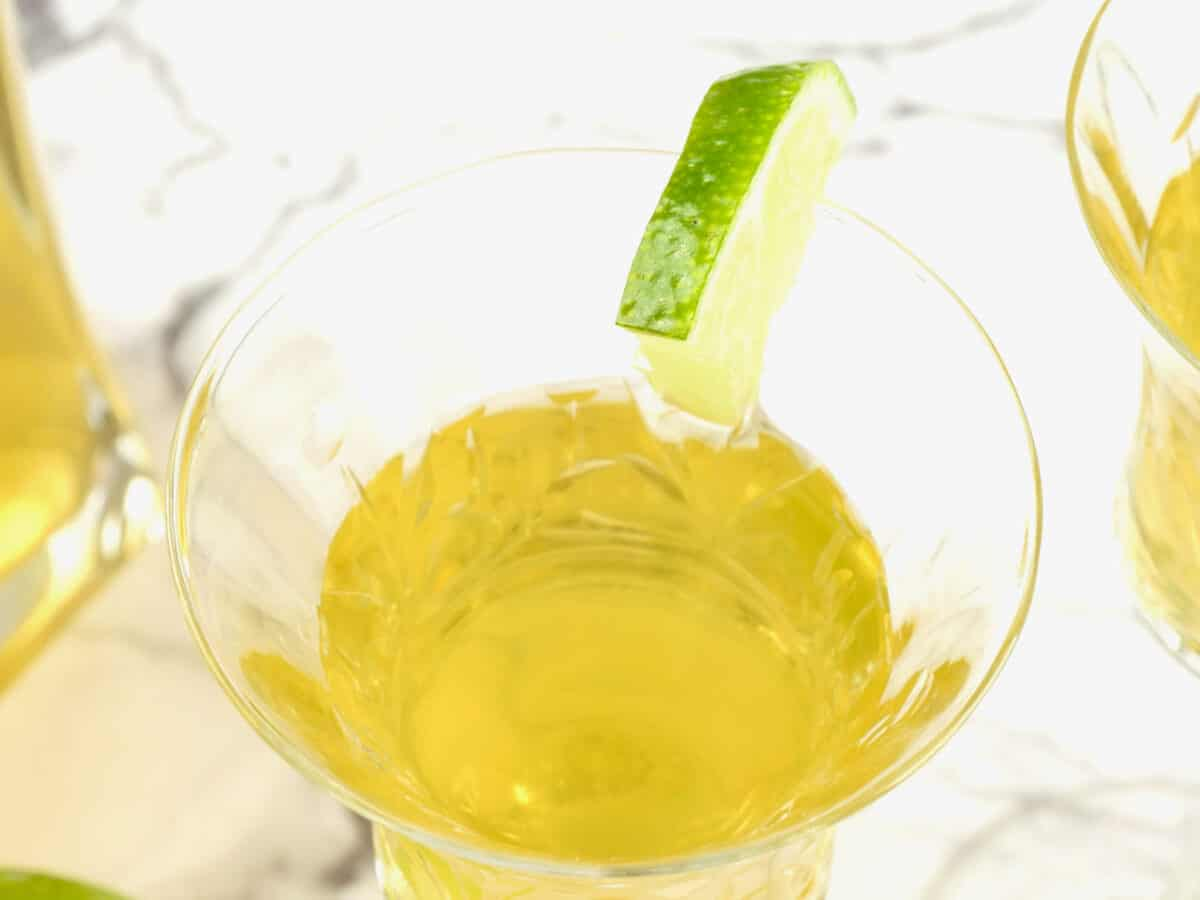 Mango liqueur served up in a sweet little liqueur glass and slice of lime
