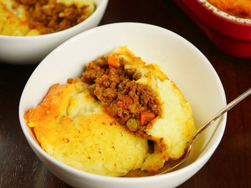 Comforting Curried Shepherd's Pie Served up in a bowl with a cheesy mashed potato layer and a rich meat filling.