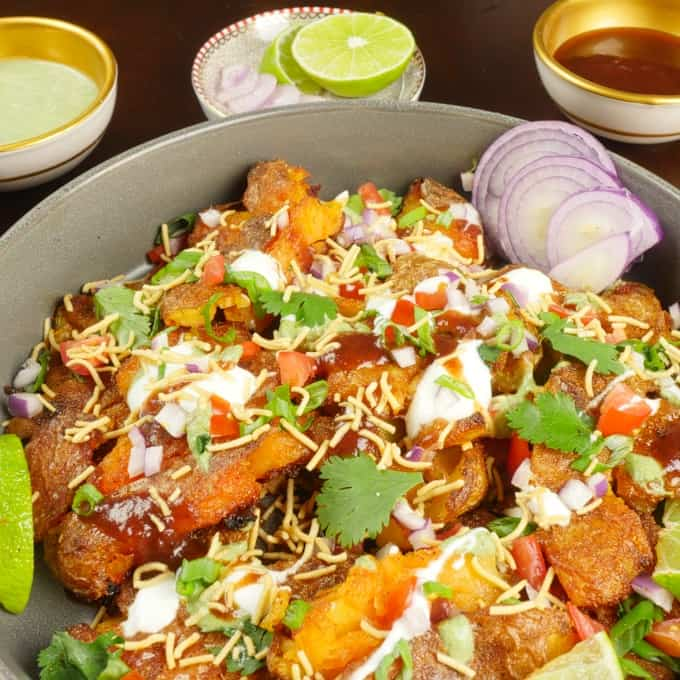Roasted Smashed Potatoes Serves as chaat with drizzles of chutney and a shower of red onion, scallion and cilantro leaves.