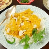 Indian Chicken Korma (Shahi Korma) served up in a pretty scalloped white bowl with plenty of orange sauce, a drizzle of yogurt and a sprinkle of cilantro.