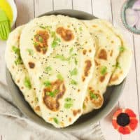 Easy Naan with Yeast Served in a basket garnished with a flutter of chopped cilantro and sprinkling of onion or nigella seeds.