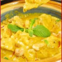 Cooked and dished out in a dark yellow ceramic bowl garnished with mint and served with fluffy basmati rice.